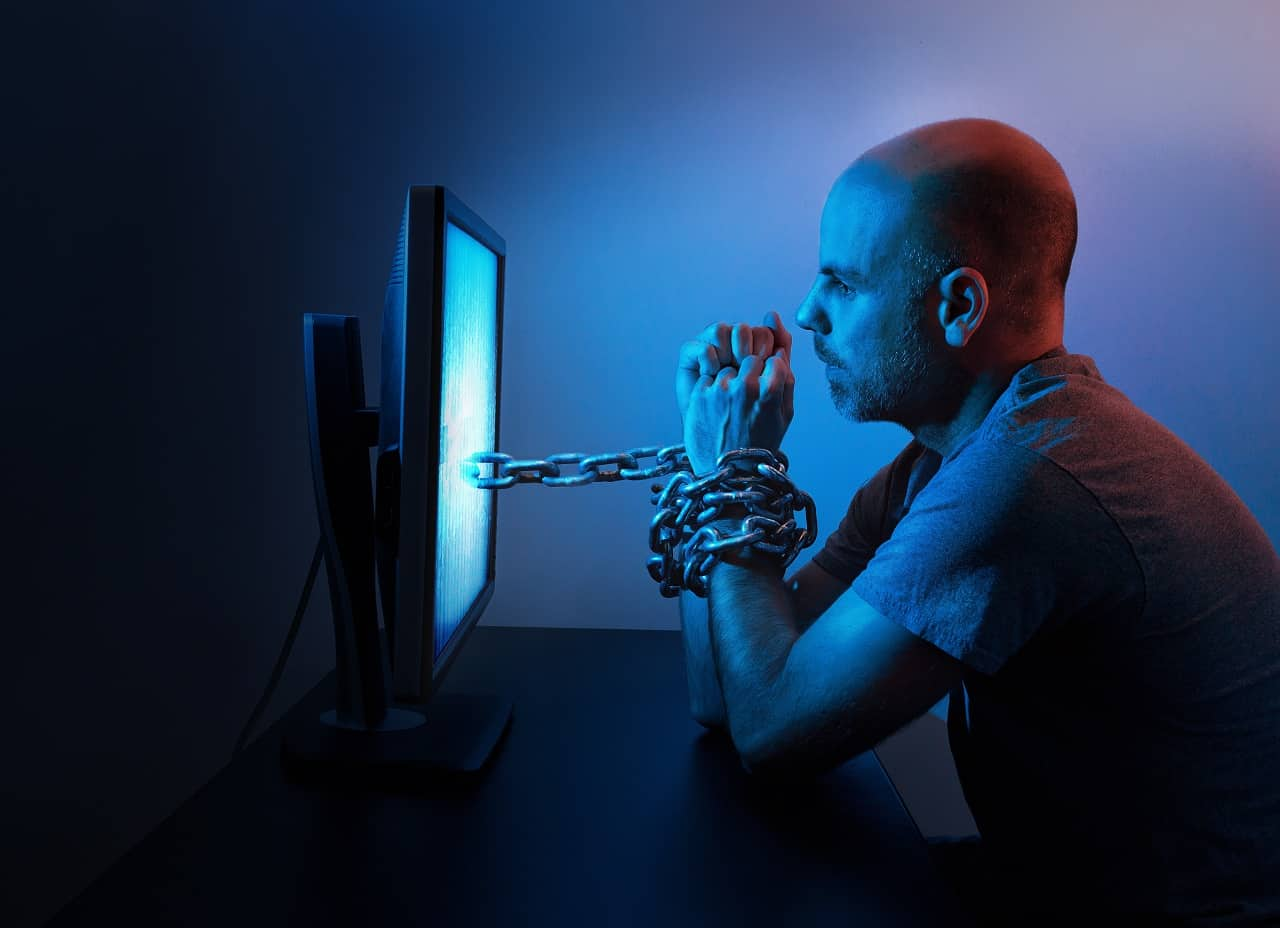 The Catholic Alpha Radical Podcast man in front a computer screen with chains on his wrists