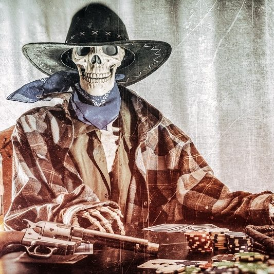21 reasons for the moral decay of sociiety and toxic masculinity ain't it (a cowboy skeleton sitting at a table with a cowboy hat, scarf, gun, bottle of whiskey, poker cards, and chips)