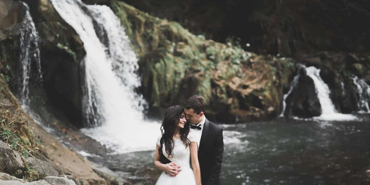 Elegant stylish happy brunette bride and gorgeous groom on the background of a beautiful river in the mountains.