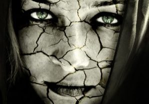 Relationship solutions a woman with a cracked face and green eyes with long hair.